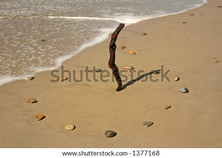 Surf drifts up close to a beach sundial at 1 PM - stock photo