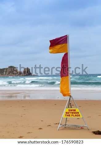 Surf life-saving flags at the beach with warning to swim between the flags - stock photo