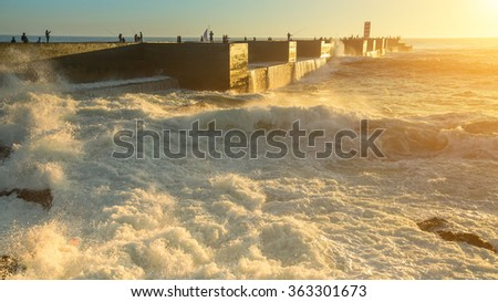 Surf near the stone pier on the ocean during the sunset. - stock photo