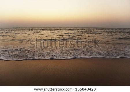 Surf on the beach at dusk, Goa, India - stock photo