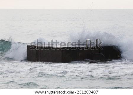 Surf on the pier. Atlantic Ocean. - stock photo