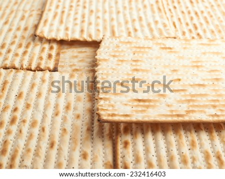 Surface covered with machine made matza flatbread as a background texture, shallow depth of field composition - stock photo