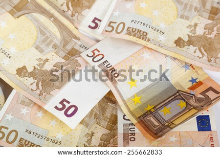 Surface covered with multiple bank note euro banknotes over the white background - stock photo
