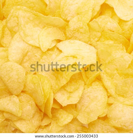 Surface covered with yellow wavy potato chips snacks as a background composition - stock photo