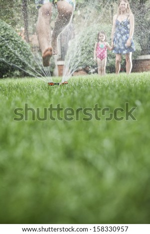 Surface level shot of father jumping through sprinkler in the grass - stock photo