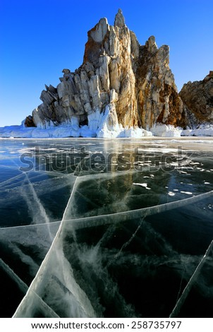 Surface of frozen lake Baikal. Cliff rock with icicles. - stock photo