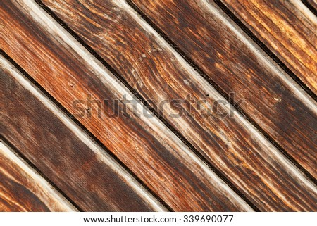 Surface of old wooden brown planks (wooden wall), arranged on a diagonal suitable for use as background. - stock photo