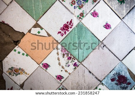 Surface of the old and partly damaged square tiles with different design. - stock photo