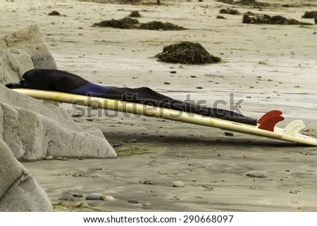 Surfboard leaning on rocks at Swami's Beach in San Diego California - stock photo