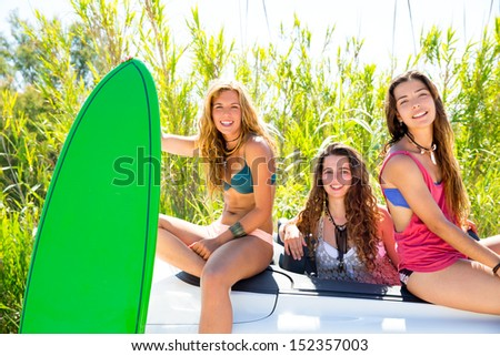 surfer beautiful girls group holding happy surfboards on convertible car - stock photo