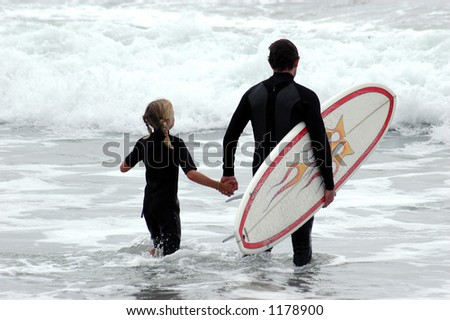 Surfer Dad and his young daughter entering the water together. - stock photo