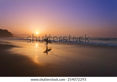 surfer entering water at the sunset - stock photo