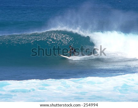 Surfer gets in the pipe on Maui's north shore. - stock photo