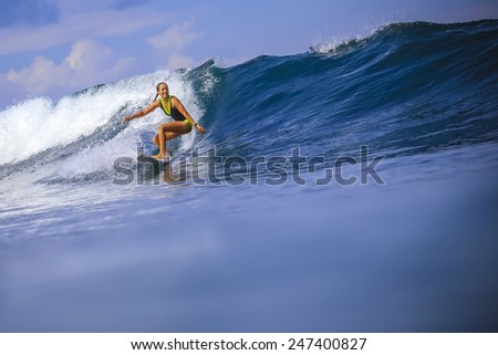 Surfer girl on Amazing Blue Wave, Bali island. - stock photo