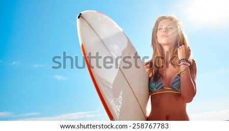 surfer girl posing with her surfboard - stock photo