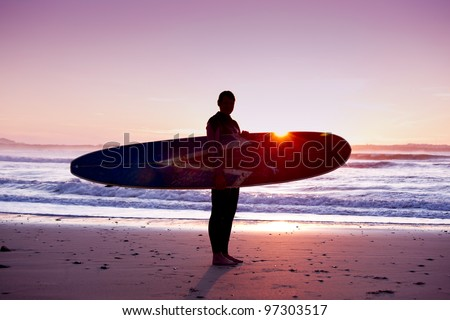 Surfer girl with surfboard at sunset beach - stock photo