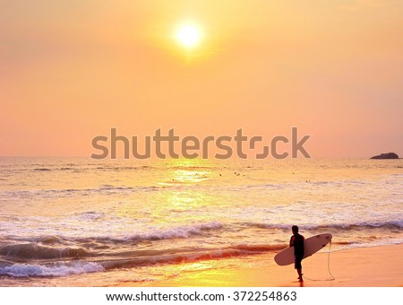 Surfer going to the ocean for surfing at sunset. - stock photo
