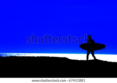 surfer heading out for a final run silhouetted against a blue sky - stock photo