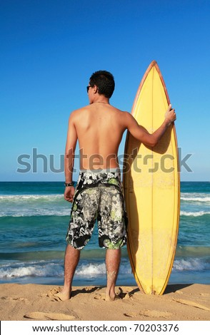Surfer holding a surf board on beach - stock photo