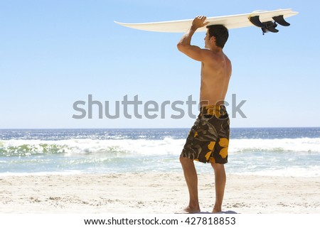 Surfer holding a surf board on tropical beach - stock photo