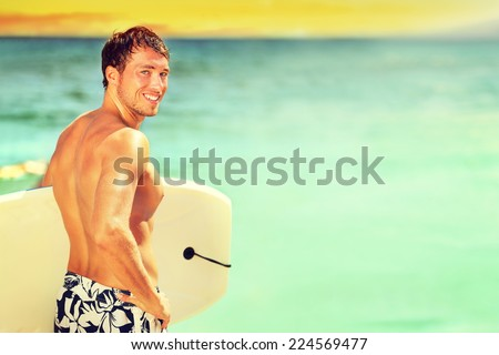 Surfer man going surfing on summer beach. Male bodyboarding surfing man good looking standing with bodyboard surfboard during vacation holidays getaway. Caucasian water sport model in his 20s. - stock photo