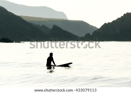 surfer man silhouette in solitary beach with  flat sea at sunset - stock photo