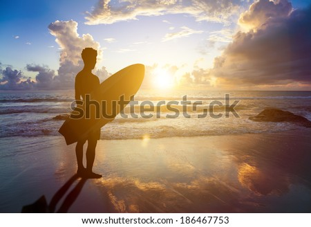 surfer man standing on beach and holding a surfboard - stock photo