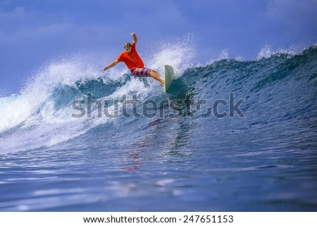 Surfer on Amazing Blue Wave, Bali island. - stock photo