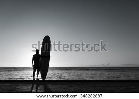 Surfer on Beach at Sunset - stock photo