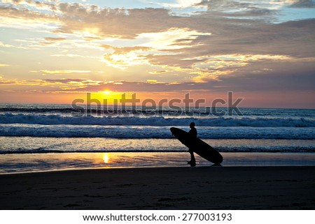 Surfer on the beach at sunset - stock photo