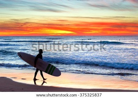 Surfer on the ocean beach at colorful sunset. Portugal - stock photo