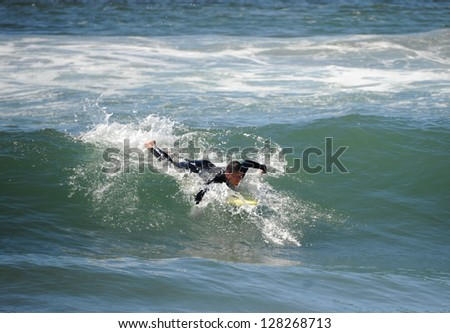 Surfer paddling to catch a wave in California. - stock photo