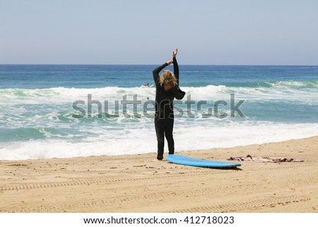 Surfer putting on a wetsuit on the beach - stock photo