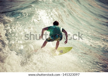 Surfer Rides a Large Blue Tropical Wave in Paradise - stock photo