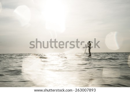 surfer silhouette with lens flares effect. - stock photo