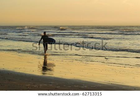 Surfer walking the Grand Isle beach in Louisiana at sunrise. - stock photo