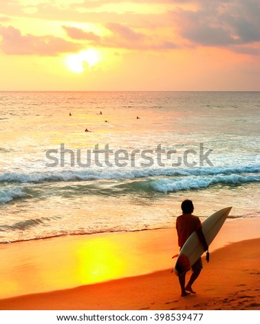 Surfer with a surfboard on the beach at sunset. Sri Lanka - stock photo