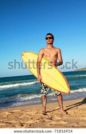 Surfer with a surfboard on tropical beach - stock photo