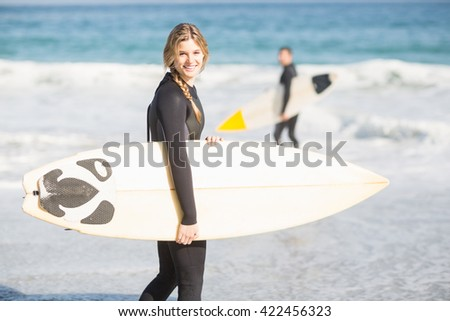 Surfer with a surfboard walking on the beach on a sunny day - stock photo