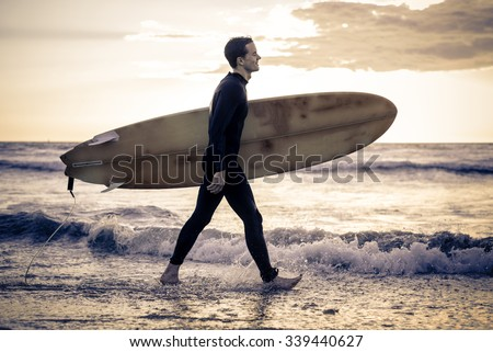 Surfer with board walking along the ocean - Sportive man going to surf on a tropical beach - stock photo