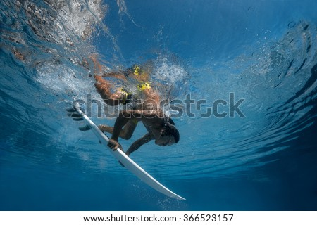 Surfer with surf board dive underwater with fun under big ocean wave - stock photo