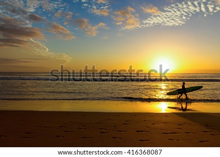 Surfer with surfboard in the sunrise scenery at Manly Beach,Australia - stock photo