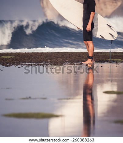 Surfer with surfboard on a coastline of Bali, Indonesia - stock photo