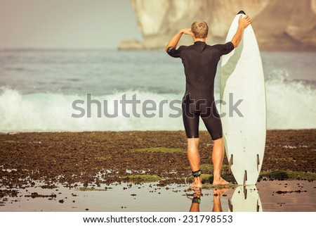 Surfer with surfboard on a coastline of Sumbawa, Indonesia - stock photo