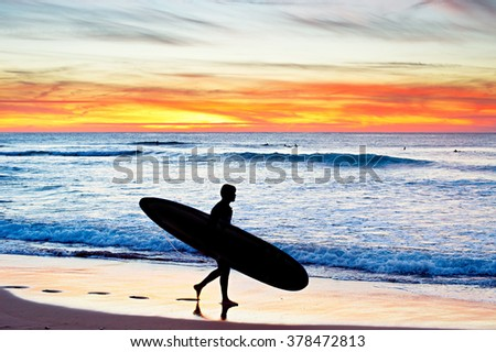 Surfer with surfboard walking on the beach at sunset. Portugal - stock photo