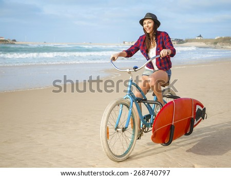 Surfer young woman riding her bicycle on the beach - stock photo