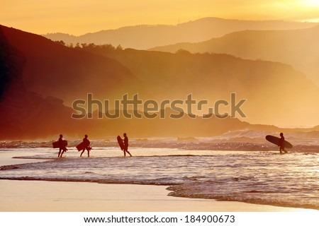 surfers and boogie boards on beach at sunset - stock photo