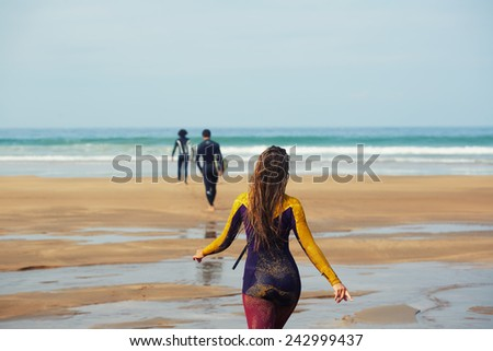 Surfers carrying their surfboard going to the sea, surfers in diving suits ready to surf walking to the ocean - stock photo