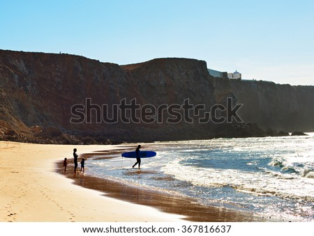 Surfers family on the beach in the bright sunny day. Portugal - stock photo
