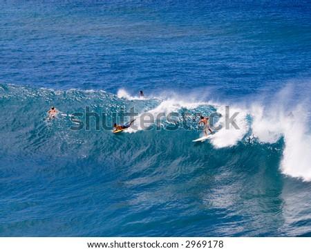 Surfers in Maui, Hawaii enjoying the waves. - stock photo